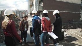Os homens e as mulheres nos capacetes de segurança que falam perto da câmara de visita concreta soam no terreno de construção vídeos de arquivo