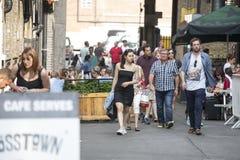 Os homens e a mulher do moderno vestiram-se no estilo fresco do londrino que andam na pista do tijolo, uma rua popular entre povo Imagem de Stock Royalty Free