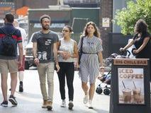 Os homens e a mulher do moderno vestiram-se no estilo fresco do londrino que andam na pista do tijolo, uma rua popular entre povo Fotografia de Stock Royalty Free