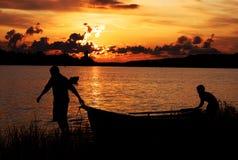 Os homens empurram o barco Fotografia de Stock