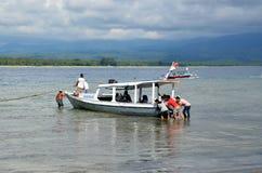 Os homens empurram um barco encalhado Fotos de Stock Royalty Free