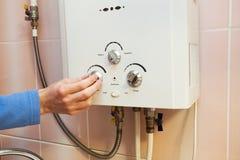 Os homens entregam regulam o poder da água quente no aquecedor de água do gás imagem de stock royalty free
