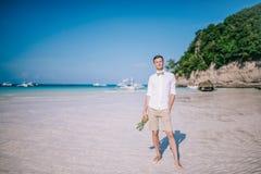 Os homens estão em um Sandy Beach branco pelo oceano Os homens estão guardando um abacaxi em sua mão Imagem de Stock