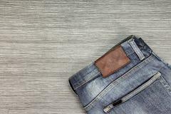 Os homens formam, calças de ganga em um fundo de madeira marrom fotografia de stock royalty free