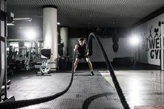 Os homens fortes com corda da batalha lutam cordas exercitam no gym da aptidão Crossfit fotos de stock