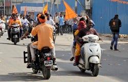 Os homens indianos montam a bicicleta do 'trotinette' e do motor, acenando bandeiras religiosas hindu durante o yatra hindu do de fotografia de stock royalty free