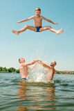 Os homens jogaram o menino na água Imagem de Stock Royalty Free