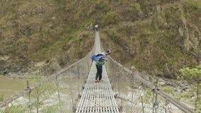 Os homens locais levam uma carga pesada na ponte de suspensão sobre o rio em Nepal video estoque