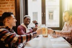 Os homens multi-étnicos consideráveis são copo do tinido da cerveja que fala que sorri ao descansar no bar foto de stock royalty free