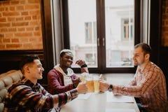 Os homens multi-étnicos consideráveis são copo do tinido da cerveja que fala que sorri ao descansar no bar imagem de stock royalty free