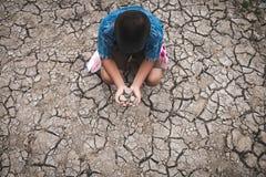 Os homens na terra racharam seco devido à seca imagens de stock royalty free