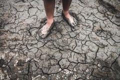 Os homens na terra racharam seco devido à seca imagem de stock royalty free