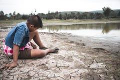 Os homens na terra racharam seco devido à seca fotografia de stock