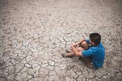 Os homens na terra racharam seco devido à seca foto de stock