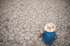 Os homens na terra racharam seco devido à seca fotos de stock royalty free