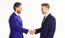 Os homens nos ternos ou nos homens de negócios guardam as mãos no aperto de mão Imagem de Stock