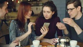 Os homens novos alegres e os amigos próximos das mulheres estão usando o smartphone e estão falando ao ter o almoço no café agrad filme