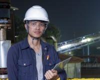 Os homens novos asiáticos verificam a máquina dentro da fábrica industrial imagem de stock