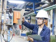 Os homens novos asiáticos verificam a máquina dentro da fábrica industrial fotografia de stock