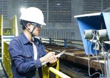 Os homens novos asiáticos verificam a máquina dentro da fábrica industrial foto de stock