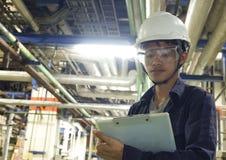 Os homens novos asiáticos verificam a máquina dentro da fábrica industrial imagens de stock royalty free