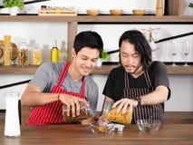 Os homens novos asiáticos vestem o avental estão derramando o cereal em uma bacia de vidro junto na tabela de madeira foto de stock royalty free