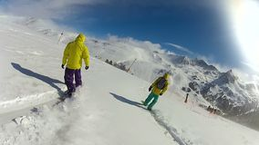 Os homens novos ativos que apreciam o snowboard montam na inclinação de montanha nevado, estilo de vida filme