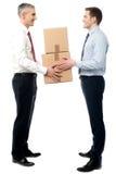 Os homens novos de sorriso recebem caixas das caixas fotografia de stock