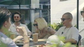 Os homens novos e a mulher asiáticos dos adultos que sentam-se em um café exterior colocam o riso de conversa de fala filme