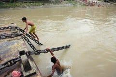 Os homens novos executam o conluio em um barco movente Imagens de Stock