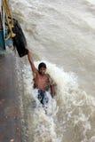 Os homens novos executam o conluio em um barco movente Imagem de Stock