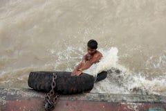 Os homens novos executam o conluio em um barco movente Foto de Stock