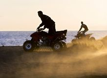 Os homens novos no quadrilátero bikes na praia arenosa durante o por do sol imagem de stock royalty free