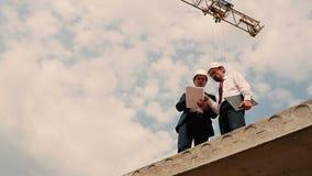 Os homens olham o plano da construção no canteiro de obras video estoque
