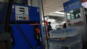 Os homens que tailandeses os povos conduzem o carro vão encher o óleo no posto de gasolina em Banguecoque, Tailândia video estoque