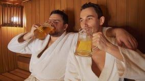 Os homens relaxam no banho, sauna, cerveja da bebida vídeos de arquivo