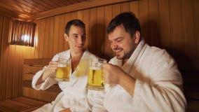 Os homens relaxam no banho, sauna, cerveja da bebida filme