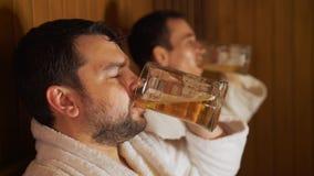 Os homens relaxam no banho, sauna, cerveja da bebida video estoque