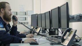Os homens sérios da vista lateral no uniforme sentam e olham monitores