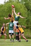 Os homens saltam para a bola no jogo de futebol amador das regras do australiano foto de stock
