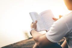 Os homens sentam o livro de leitura na natureza quieta imagens de stock royalty free