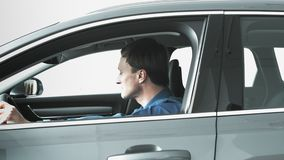 Os homens sentam-se no carro novo vídeos de arquivo