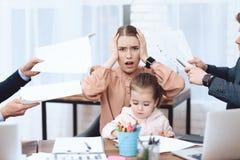Os homens têm uma queixa sobre uma mulher que venha com sua filha trabalhar fotografia de stock royalty free