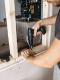 Os homens trabalham com uma chave de fenda, fixando um quadro de madeira para uma janela em sua casa imagens de stock