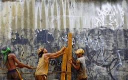 Os homens trabalham duramente junto para erigir logs de madeira fotografia de stock