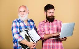 Os homens trabalham escrevendo dispositivos Gera??o velha Tecnologias de Digitas Homem superior com máquina de escrever e moderno imagem de stock royalty free