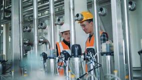 Os homens verificam máquinas da cervejaria, fim acima video estoque