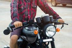 Os homens vestem uma camisa de manta vermelha, conduzem uma motocicleta do vintage Foto de Stock Royalty Free
