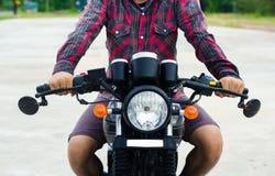 Os homens vestem uma camisa de manta vermelha, conduzem uma motocicleta do vintage Fotografia de Stock