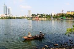 Os homens vietnamianos em um barco limpam o lago ocidental Imagens de Stock